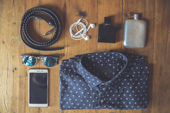 Clothing and essentials for traveling light over a wooden board. Aerial view of clothing and essentials for traveling light over a wooden board Royalty Free Stock Photography