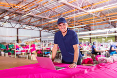 Clothing factory manager. Portrait of senior clothing factory manager with laptop computer stock images