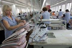Clothing Factory Workers. Pazardjik, Bulgaria - January 13, 2011: Woman arranges finished shirts in clothing factory, in Pazardjik royalty free stock image