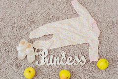 Clothing and footwear for babies and apples Royalty Free Stock Image