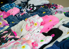 Clothing at Garage Sale. A collection of colorful kids` clothing arranged with prices on a table at a garage sale Royalty Free Stock Images