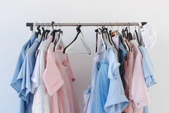 Clothing on hangers. Side view of different female clothing on hangers on background of white wall Royalty Free Stock Image