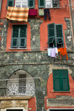 Clothing hanging from apartment windows in Manarola Italy. Clothing and laundry hang out to dry from shuttered windows in the village of Manarola in the Cinque Royalty Free Stock Photography