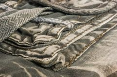 Clothing items washed cotton fabric texture with seams, clasps, buttons and rivets. Macro, close-up stock image
