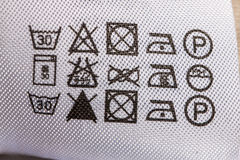 Clothing label with laundry care instructions. Symbols on care of clothes closeup royalty free stock photo