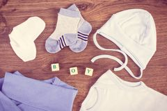 Clothing for newborn baby and word boy, extending family and expecting for kids. Blue clothing for newborn baby and word boy, concept of expecting for kids and stock images