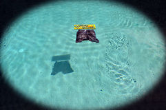 Clothing Optional. This is a photo of a sign and cloths floating in a pool Royalty Free Stock Images