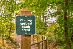 Clothing optional sign on post on trail to beach, British Columb stock image