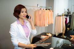 Clothing shop manager. Pretty clothing shop manager calling on the phone Royalty Free Stock Images