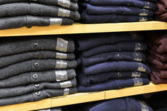 Clothing stacked neatly on the shelf in fashion shop Royalty Free Stock Photography