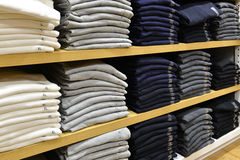 Clothing stacked neatly on the shelf in fashion shop Royalty Free Stock Images