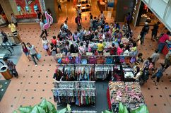 Clothing stalls, shoes and bags on display at shopping mall. The foyer of Jurong Point Shopping Mall in Singapore's west district is used for selling clothing by Royalty Free Stock Images