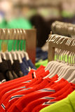 Clothing store. A lot of shirts hanging in a clothing store Stock Image