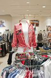 Clothing store. Close up of the mannequin and multicolored shirts on the rack in the clothing store Royalty Free Stock Image