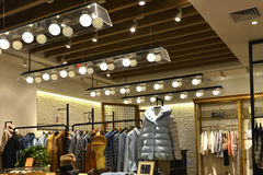 Clothing store. Interior view of a fashion shop,Hongkong,China,Asia. decorated with pendant lamps and led lights Stock Photos