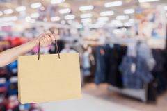 Clothing store in shopping mall defocused blur background. Woman hand hold shopping bag over clothing store in shopping mall defocused blur background with bokeh Royalty Free Stock Photography