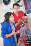 Clothing Switch. Latino and Caucasian men can't explain clothing switch in laundromat Stock Photography