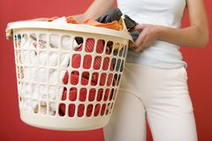 Clothing to the washing. Woman standing and holding in hands full laundry basket. Closeup on basket. Front view royalty free stock photo