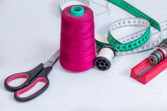 Clothing accessories,thread, scissors and measuring tape. Clothing tools and accessories closeup, scissors, threads and needles royalty free stock images