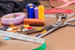 Clothing accessories,thread, scissors and measuring tape. Clothing tools and accessories closeup, scissors, threads and needles royalty free stock photography
