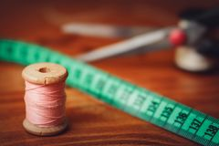 Clothing accessories,thread, scissors and measuring tape. Clothing tools and accessories, scissors, measuring tape, and a roll of thread royalty free stock photo
