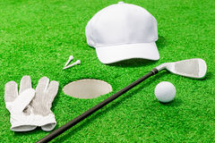 Clothing and tools for the game of golf near the hole Stock Image