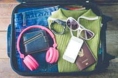 Clothing traveler`s Passport, wallet, glasses, watches, smart phone devices, on a wooden floor in the luggage ready to travel.  stock photography