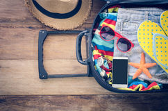 Clothing traveler`s , wallet, smart phone devices, on a wooden Stock Photo