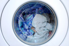 Clothing in washing machine. Close up of a washing machine Royalty Free Stock Photography