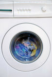 Clothing in washing machine. The drum is spinning and the contents blurred Royalty Free Stock Images