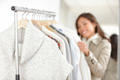 Clothing - woman shopping clothes. Clothing. Woman shopping clothes in store looking at clothing rack. Focus on winter sweater in foreground Stock Photo