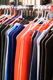 Cloths street sale. Colourful clothing and sport wear on market street sale, china textile on hangers for sale. Background Stock Photos