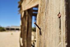 Clou dans la fin en bois  Bâtiment ruiné dans le désert Images stock
