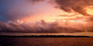 Cloud bank highlighted sunset seascape. Stock Photos
