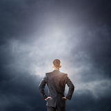Cloud and businessman looking at empty space. With hands on hips Stock Photo