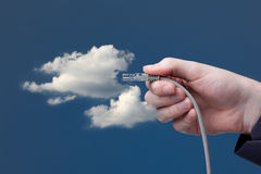 Cloud computing. Concept. Hand with ethernet cable connecting into cloud Stock Image