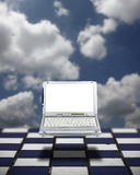 Cloud Computing. A mobile computer laptop with a blank screen for copyspace text, surreally floating over a a blue and white chess board grid with a blue cloudy royalty free stock image