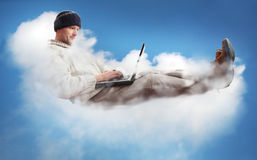 Cloud Computing. A man on a cloud operating a laptop.  The man is dressed casually to represent the majority of IT workers.  The concept is Cloud Computing