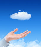 Cloud Computing Concept. Man hand propose cloud against blue sky with clouds on background. Concept image on cloud computing and eco theme Stock Image