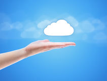 Cloud Computing Concept. Woman hand share the cloud against blue background with clouds. Concept image on cloud computing theme with copy space Royalty Free Stock Photos