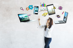 Cloud computing concept. Attractive european girl with multiple devices and drawings above. Cloud computing concept Royalty Free Stock Photography