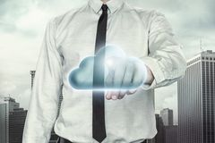 Cloud computing concept with businessman on. Cityscape background pointing towards blue cloud Stock Image
