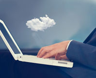 Cloud computing concept, businessman with cloud over his laptop. On blue background Royalty Free Stock Photography