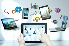 Cloud computing concept. Female hands holding and pointing at tablet with multiple devices and drawings above. Cloud computing concept Stock Photo