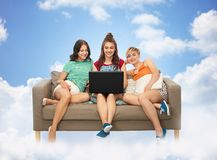 Female friends with laptop computer over clouds stock photo
