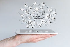 Cloud computing and mobile computing concept. Hand holding tablet or smart phone. Royalty Free Stock Image