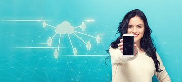 Cloud Computing with People with young woman holding out a smartphone. In her hand Royalty Free Stock Image