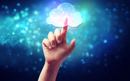 Cloud computing symbol being pressed by a persons hand. Cloud computing connectivity concept icon being pressed on a blue technology background Stock Photography