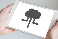 Cloud computing symbol for upload and download displayed on touch screen of modern tablet.  royalty free stock images