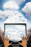 Cloud computing technology. Two hands on a laptop with a brick wall and a group of clouds traveling up to a large cloud.  Binary ones and zeros moving from Stock Images
